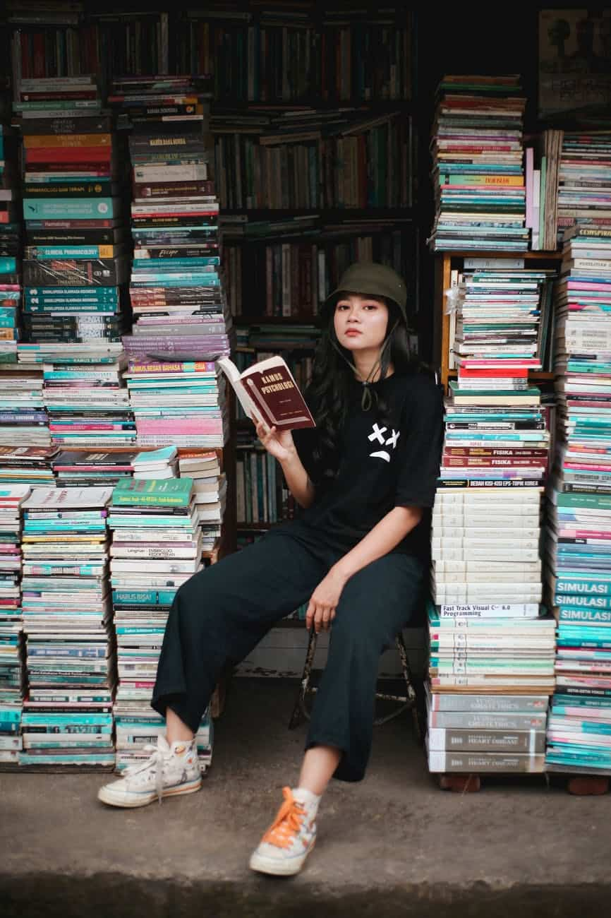 woman in black crew neck t shirt sitting on books