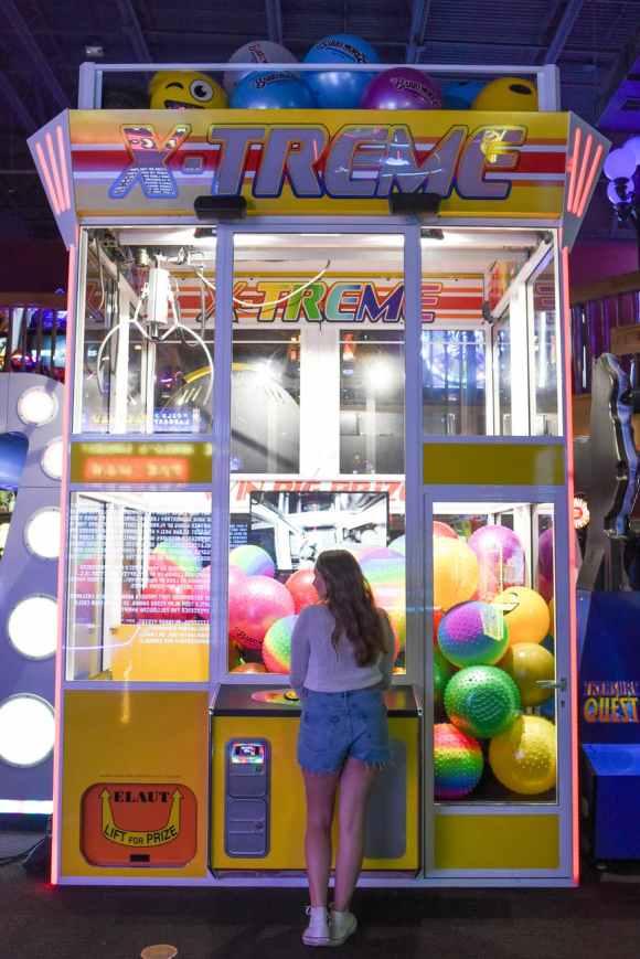 woman standing in front of x treme arcade machine komplexe Textaufgaben setzen sich aus realen Situationen zusammen.