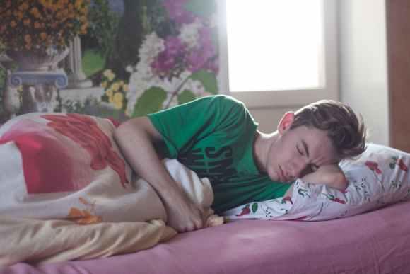 man wearing green printed crew neck shirt while sleeping Gesunder Schlaf ist wichtig für den Erfolg in der Schule und im Beruf.