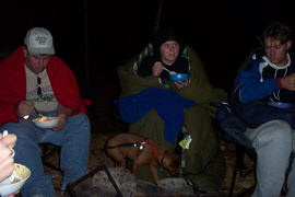 Craig, Boing, Crystal and Jas eating the fire-warmed apple crisp  Tracey made for dessert.   But it was a bit chilly (as evidenced by  the sleeping bag Crystal is wrapped up in).