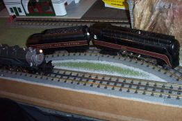 A older model steam engine passing a newer model steam engine, on an O gauge track.