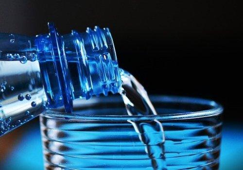 Eau de bouteille en plastique versée dans un verre