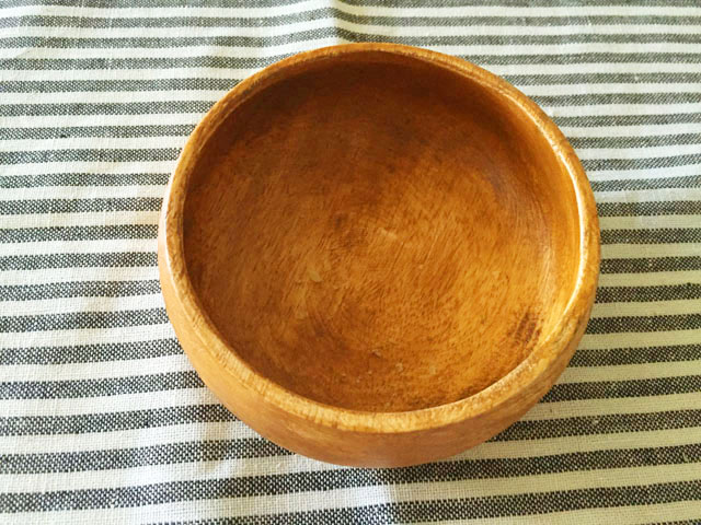 茶色と白のボーダーのランチョンマットに木のお皿を置いている
