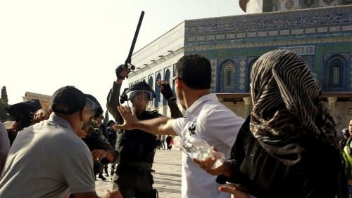 Un policier israélien lèvesa matraquesur les fidèles Palestiniens près de la mosquée Al Aqsa dans la vieille ville de Jérusalem, le 27 juillet 2017. Mahmoud Illean / AP