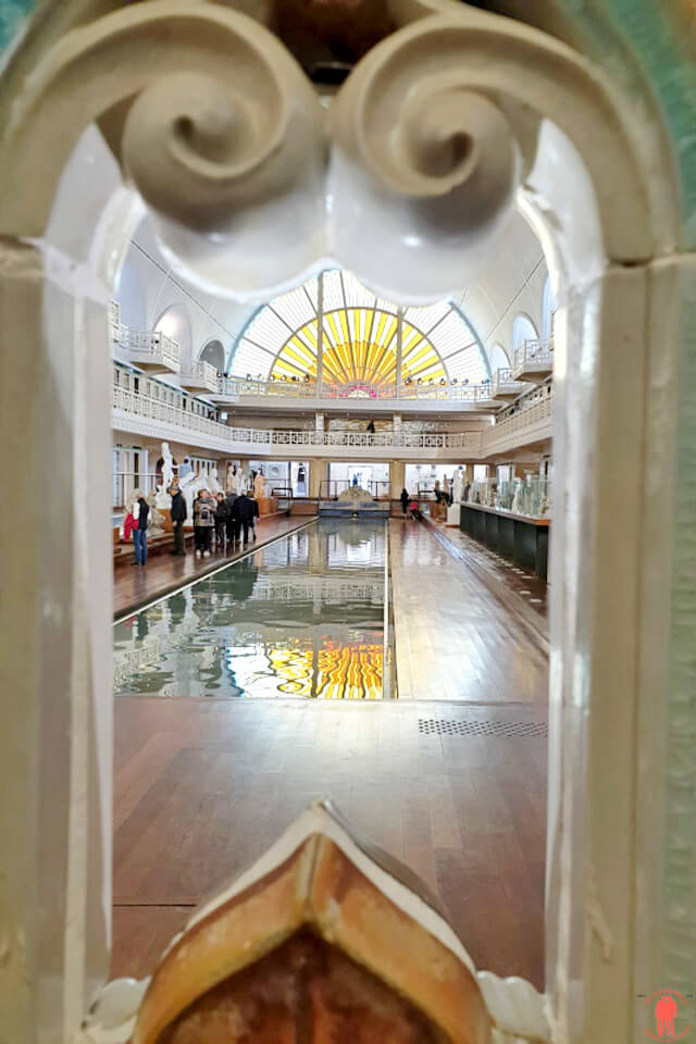Vue du bassin de la piscine de Roubaix à travers le portique d'Alexandre Sandier