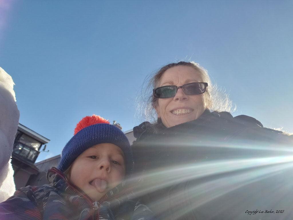 Grandmother and grandson smiling in winter sunshine