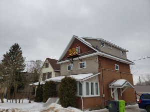 2 Yellow lawn chairs on tiny balcony at top of 3 storey house.