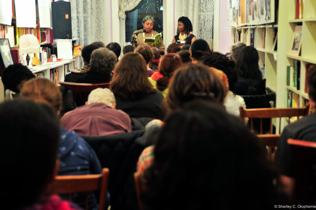 Two black lesbian activists at the front of the room holding a book affront a microphone facing a packed audience of women. Photo is taken from the back of the heads of the audience