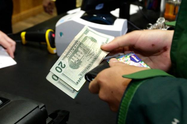 Un client paie pour son achat de marijuana récréative à Top Shelf cannabis, le mardi 8 Juillet 2014 à Bellingham, Washington, le premier jour de ventes légales de l'État. (Photo par Ted S. Warren / AP Photo)
