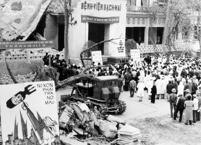 09 Jan 1973, Bach-Mai Hospital, Hanoi, North Vietnam --- Funeral services are held at Bach-Mai Hospital in Hanoi, North Vietnam for the hospital staff killed by US B-52 bombing runs on December 19-20, 1972. An anti-Nixon poster is displayed near the wreckage. --- Image by © Bettmann/CORBIS