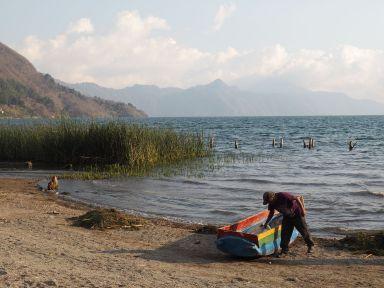 Un pêcheur avec sa barque et un tas d'algues à proximité