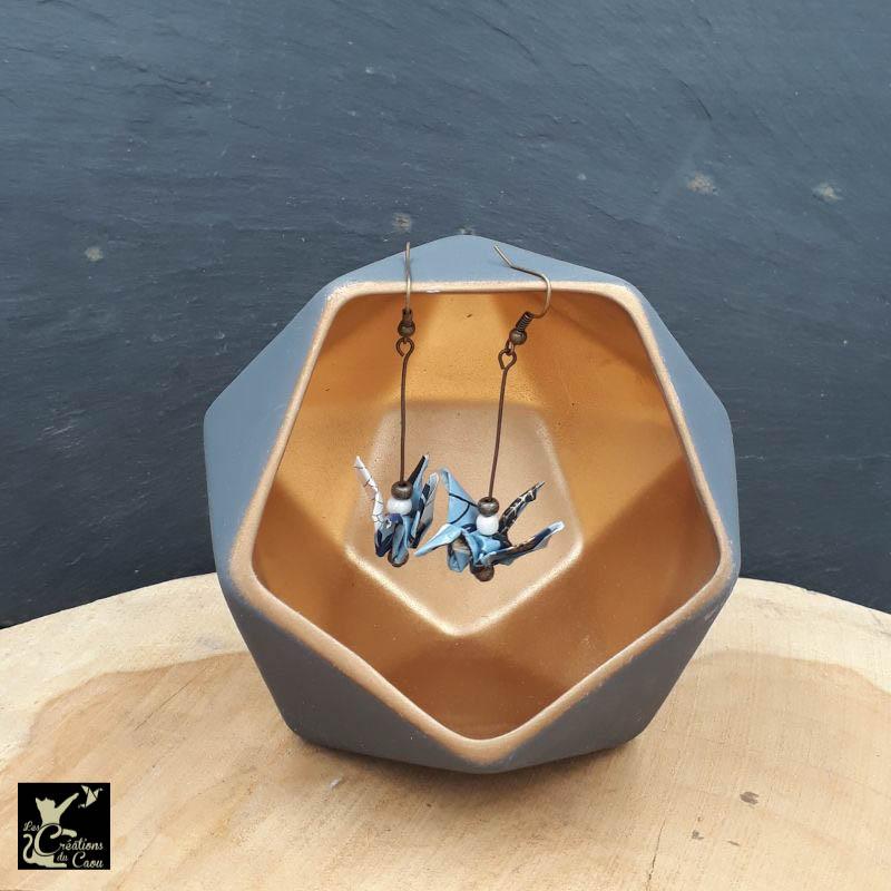 Boucles d'oreilles en origami. Le pliage est une grue traditionnelle réalisée à partir d'un papier japonais bleu ciel au motif fleuri bleu foncé et doré.