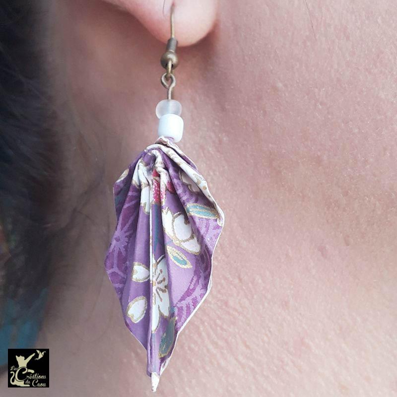 Boucles d'oreilles en origami. Le pliage est une palme réalisée à partir d'un papier japonais violet au motif fleuri de sakuras (fleurs de cerisiers) roses et blancs. Le papier est recouvert de résine afin de rigidifier et protéger le pliage.
