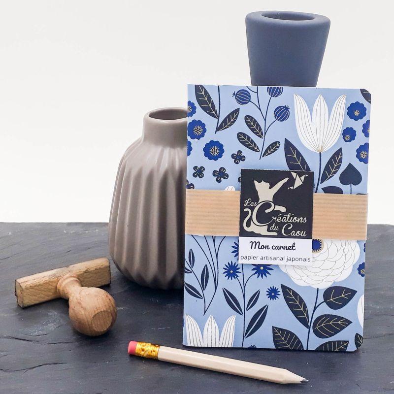 Carnet de notes au format A6. La couverture est recouverte à la main d'un papier japonais bleu ciel orné d'élégants végétaux bleus foncés et blancs.