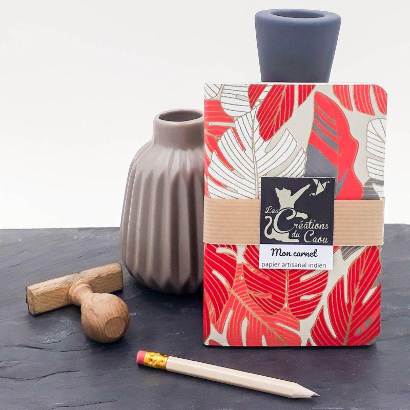 Carnet de notes au format A6. La couverture est recouverte à la main d'un papier indien orné de feuilles tropicales de couleur rouge, corail, grise.