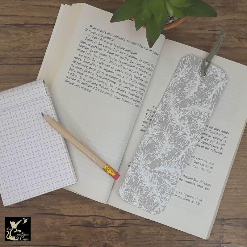 Ne perdez plus le fil de vos lectures ! Ce marque-page artisanal, recouvert d'un élégant papier indien gris au motif de plumes deviendra votre allié.