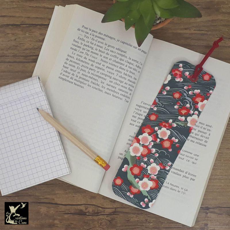 Ne perdez plus le fil de vos lectures ! Ce marque-page artisanal, recouvert d'un élégant papier japonais bleu canard orné de sakura deviendra votre allié.