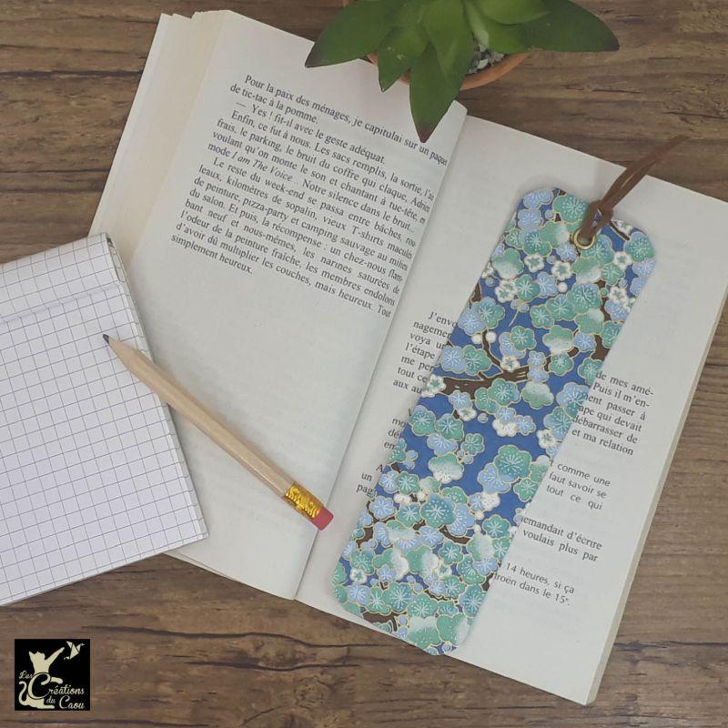 Ne perdez plus le fil de vos lectures ! Ce marque-page artisanal, recouvert d'un élégant papier japonais bleu foncé orné de fleurs de prunier deviendra votre allié.