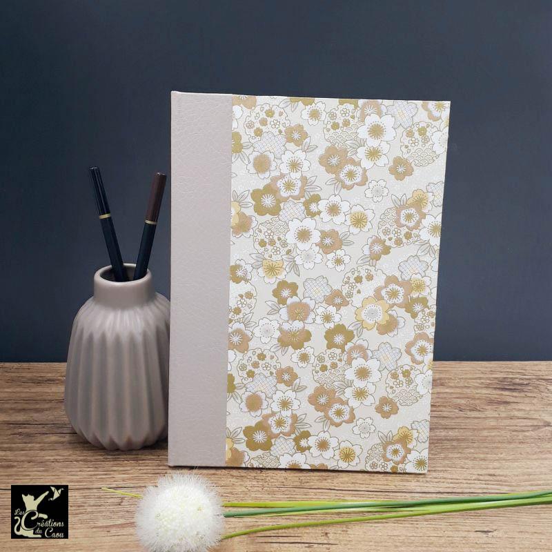 Répertoire de format A5 recouvert d'un élégant papier japonais aux tons beige et or. L'intérieur est organisé en onglets lettre par lettre.