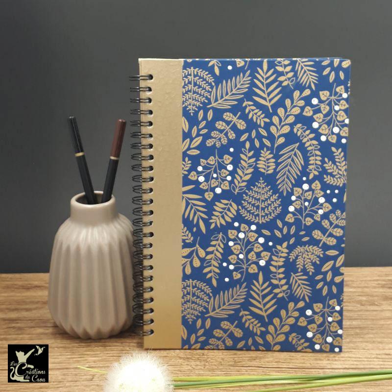 Répertoire à spirale recouvert d'un papier japonais bleu foncé orné de motifs de végétaux dorés et blancs.