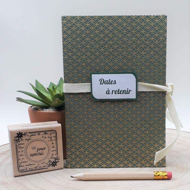Calendrier des anniversaires recouvert d'un papier artisanal japonais vert olive foncé au motif géométrique dorés, entièrement réalisé à la main dans notre atelier de Lambersart (Lille).