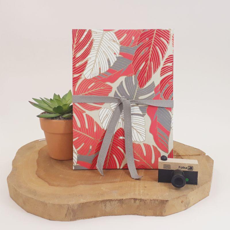 Album photo leporello réalisé à la main dans notre atelier de Lambersart (Lille), recouvert d'un papier indien au motif de végétaux exotiques rouges, corail, blanc et gris sur fond beige.