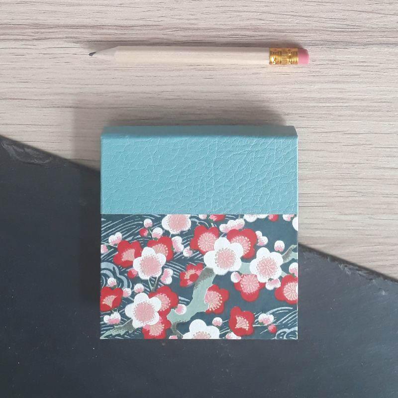 Porte bloc à post-it de la marque de papeterie lilloise : les créations du caou. Motif fleuri sur fond bleu pétrole.