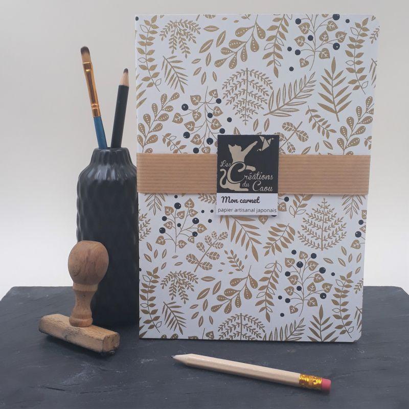 Carnet A5 recouvert à la main d'un papier artisanal japonais écru orné de motifs végétaux dorés et de baies noires.