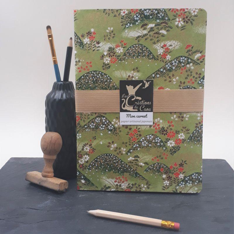 Carnet A5 recouvert à la main d'un papier artisanal japonais vert olive orné de collines fleuries.