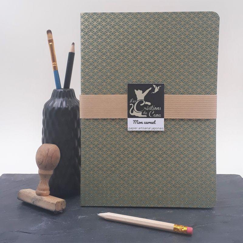 Carnet A5 recouvert à la main d'un papier artisanal japonais vert olive foncé orné d'un motif géométrique doré.