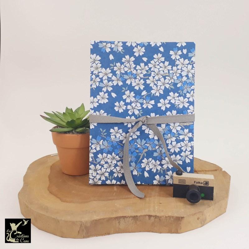 Album photo leporello réalisé à la main dans notre atelier de Lambersart (Lille), recouvert d'un papier japonais bleu marine au motif de sakuras blancs.