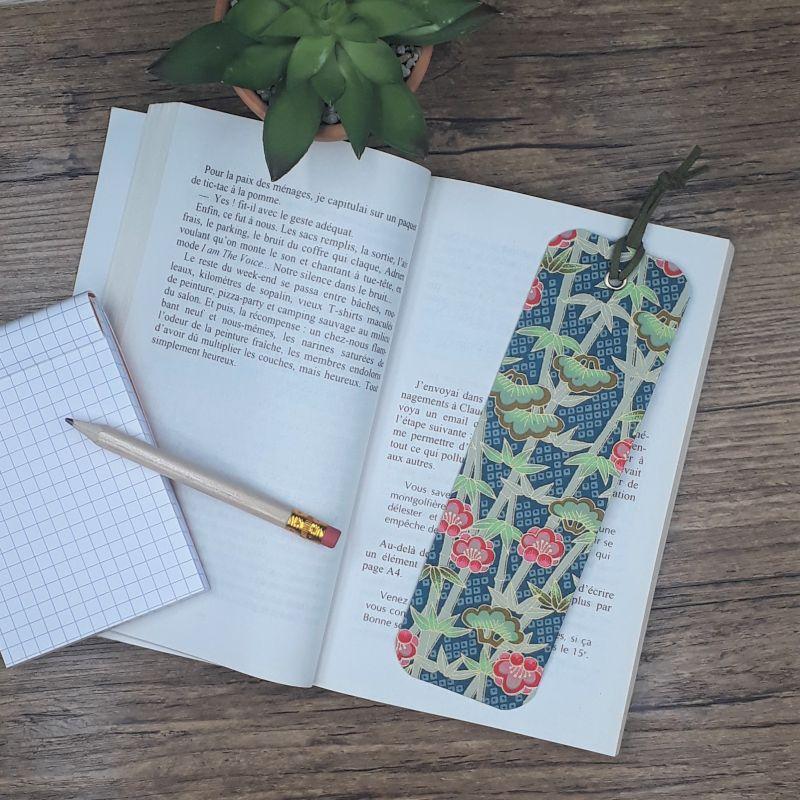 Marque-page artisanal réalisé entièrement à la main dans notre atelier de Lambersart (Lille) recouvert de papier japonais bleu canard orné de fleurs de lotus et de bambous.