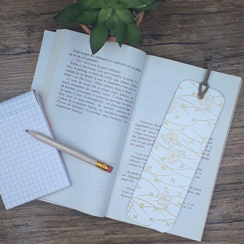 Marque-page réalisé entièrement réalisé à la main dans notre atelier de Lambersart (Lille) recouvert de papier artisanal japonais écru avec un motif fleuri doré.