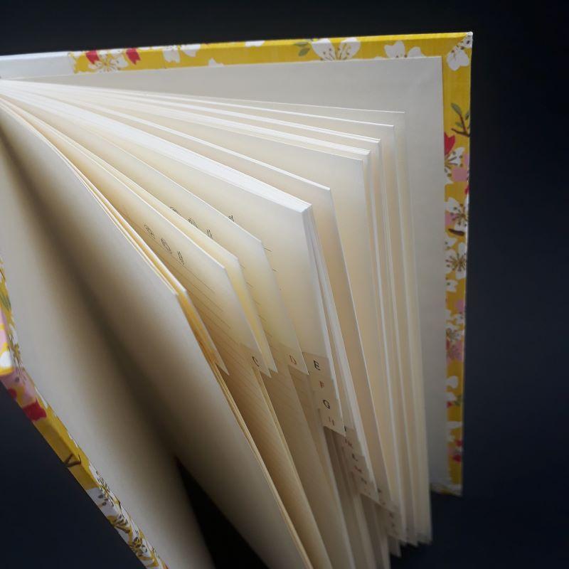 Répertoire ou carnet d'adresses jaune, motif fleuri, à onglet, dos carré collé.