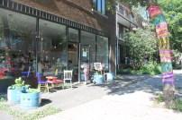 La façade avec sa vitrine, ses dessins, plantes à partager, l'arbre au tricot et petite table.