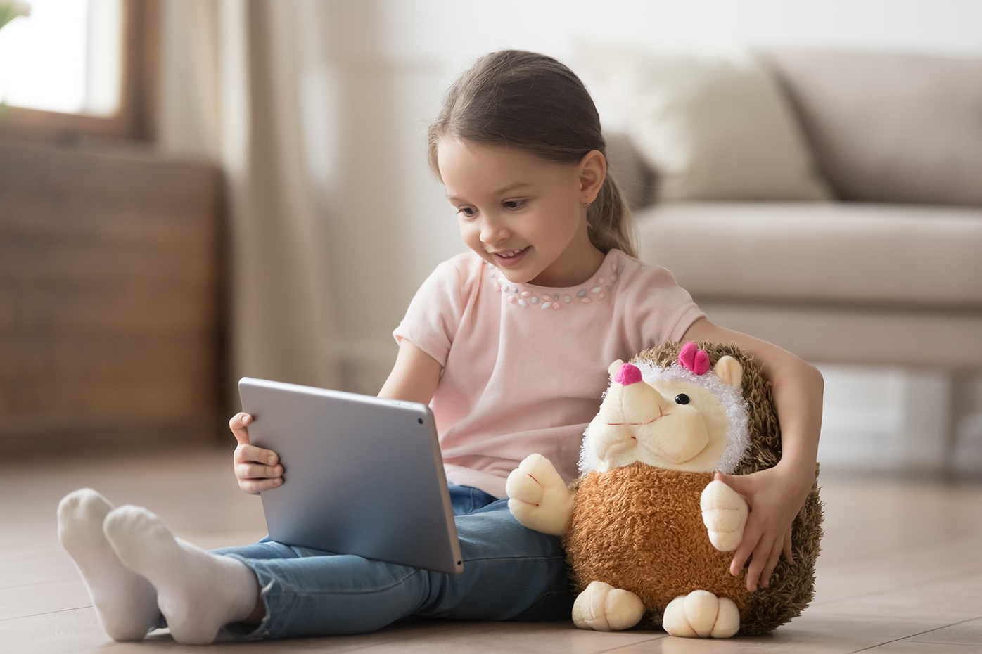 little girl and plush hedgehog looking at tablet
