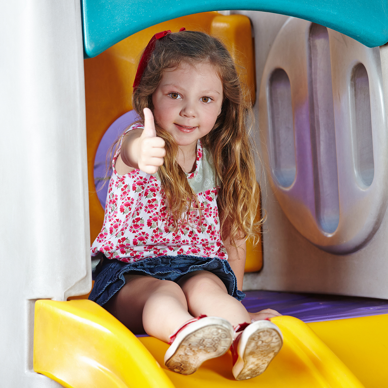 little girl with thumbs up on slide