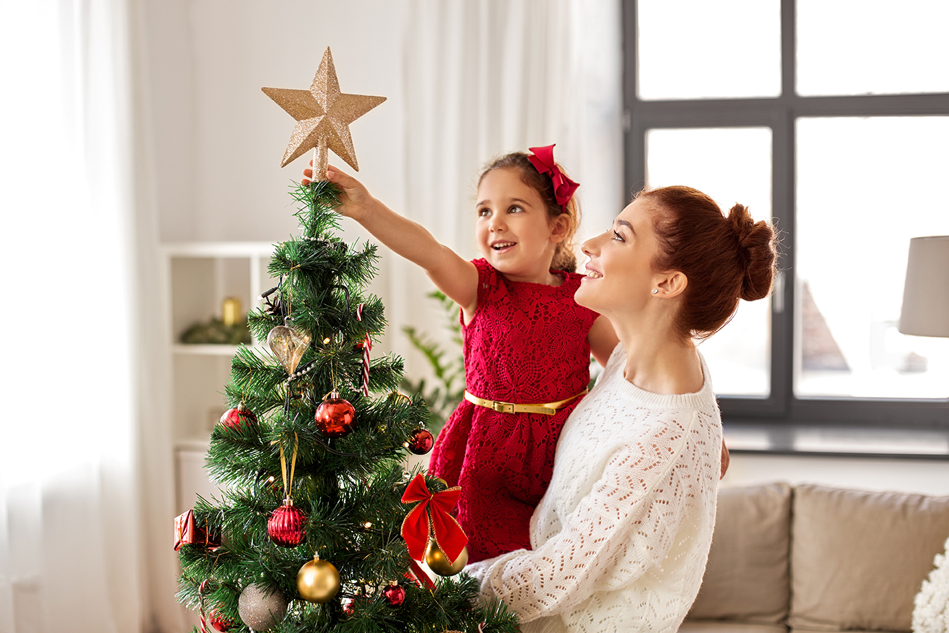 mom helping daughter put the star on top of their christmas tree