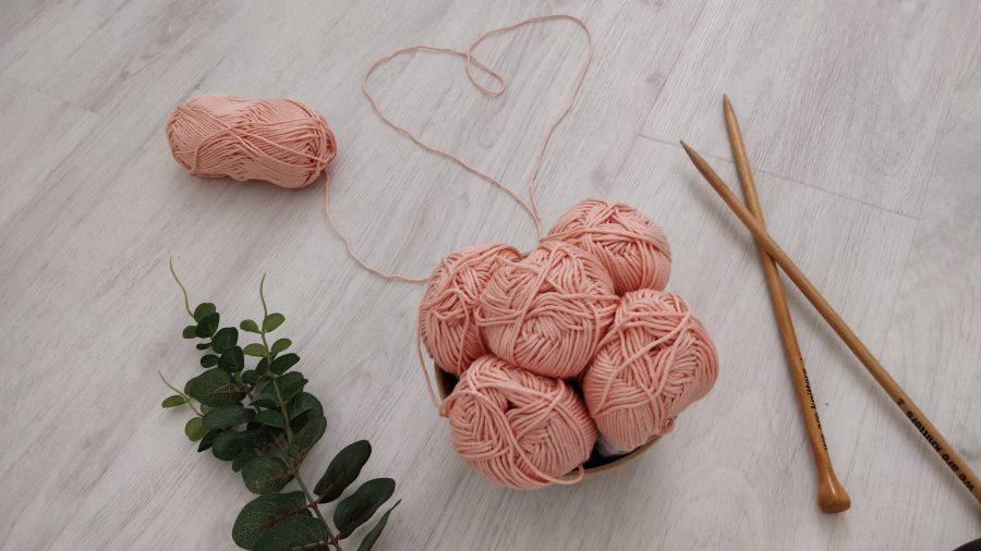 pelotes de laine roses et aiguilles droites en bois
