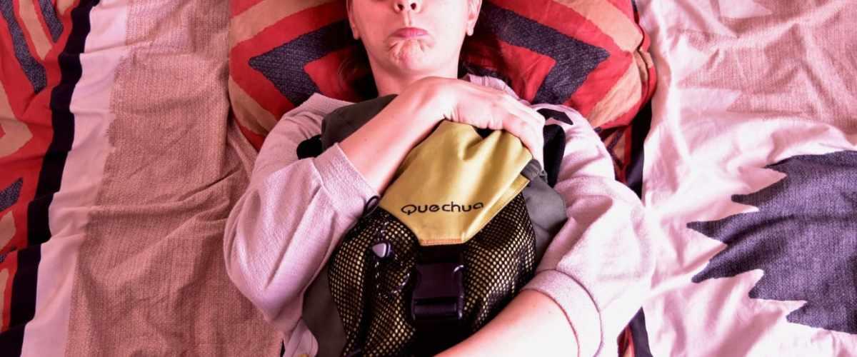 Une fille qui sert son sac de voyage contre elle, l'air angoissé.
