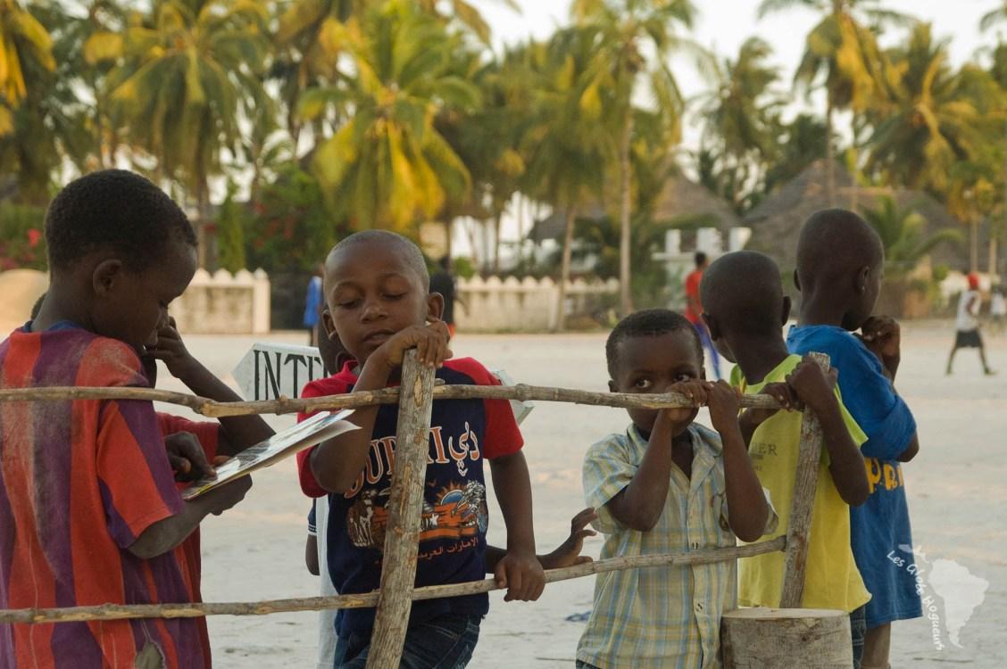 Des enfants sur la plage du village de jambiani à Zanzibar, un dvd de bruce lee à la main