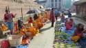 Les vendeurs de légumes font face aux vendeurs d'œillets sur Durbar Square à Katmandou