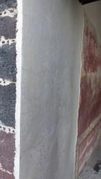 On voit bien ici la superposition des couches: sur la pierre, de la chaux est ensuite recouverte de stuc coloré