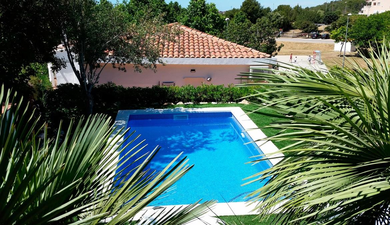 Vistas a la casa, con la piscina azul y jardín con palmeras
