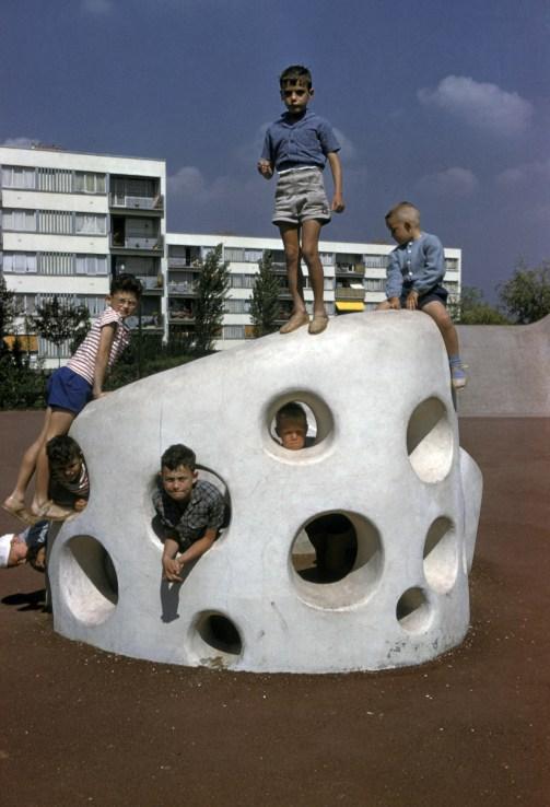 Enfants jouant sur une scultpture devant un immeuble HLM rue des Tournelles