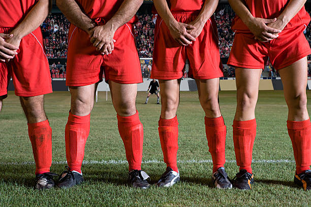 football players guarding thier groin from a ball during a set piece