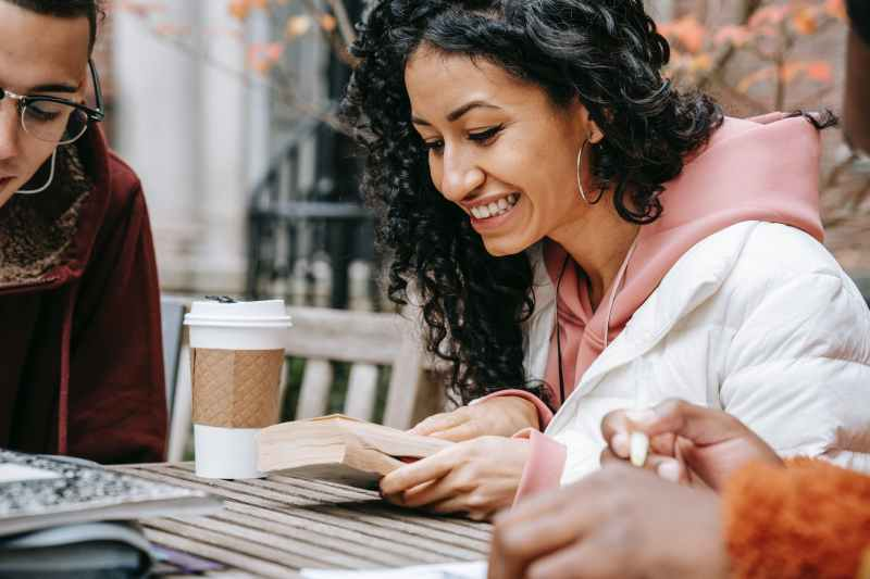 multiracial students studying with book and coffee cup in park