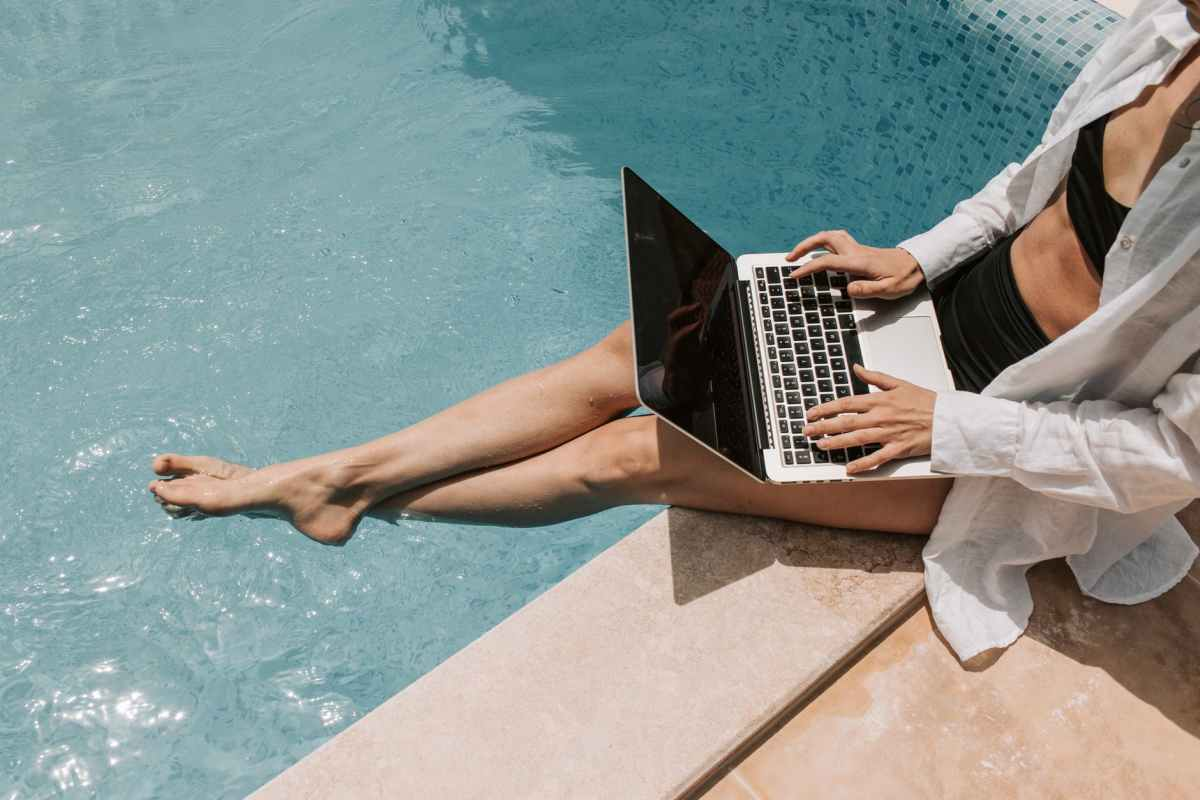 woman sitting on poolside using laptop