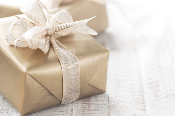 Golden gift boxes with beautiful ribbon and bow on a bright shin