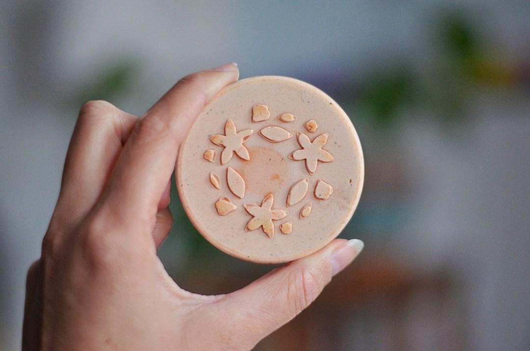 shampooing solide tenu rond par une main